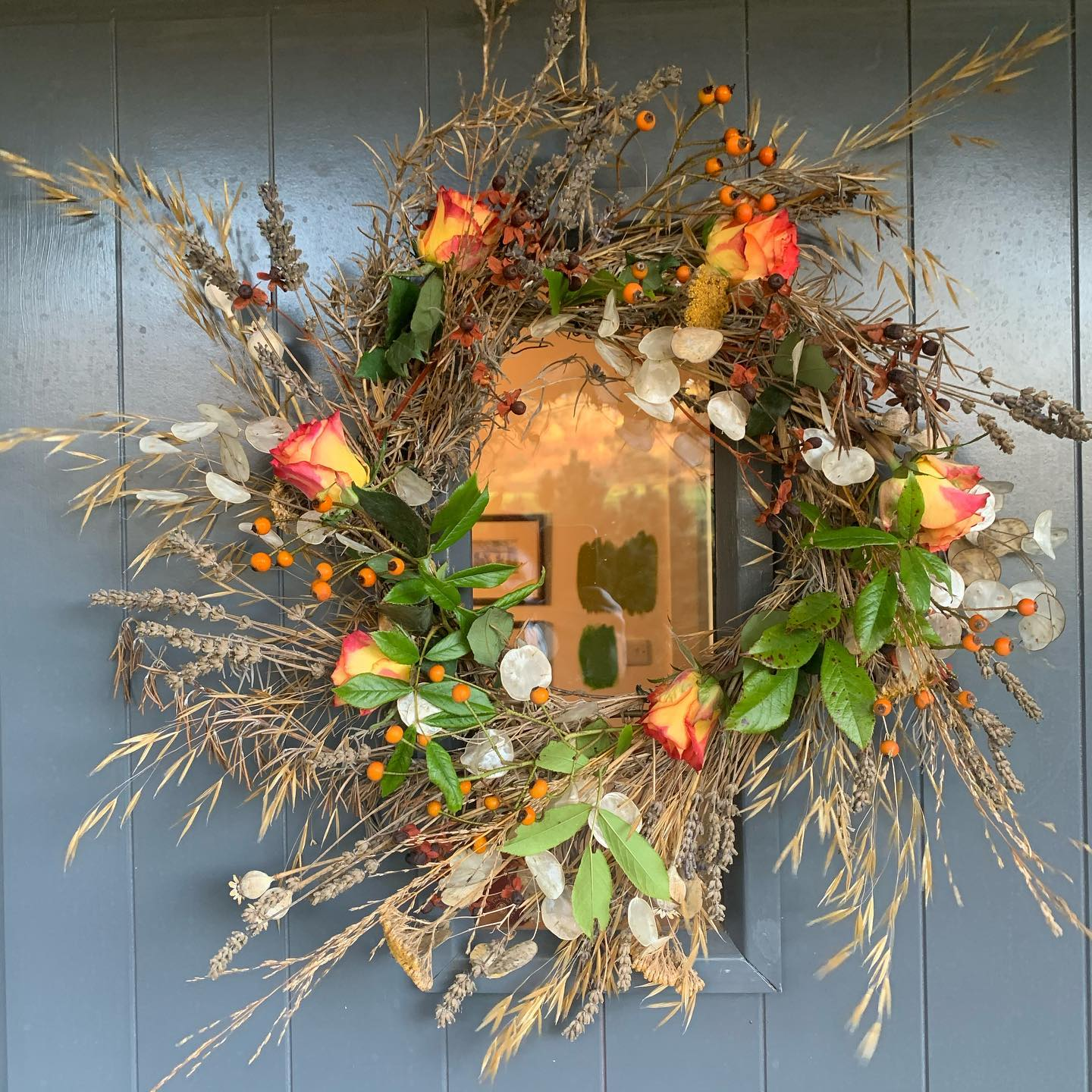 The summer door wreath (swipe right) dried brilliantly over the past couple of months and took on an autumnal buff look of it's own doing... Today a wee zhuzh adding in a bit of colour to brighten thing up using roses and rose hips.
