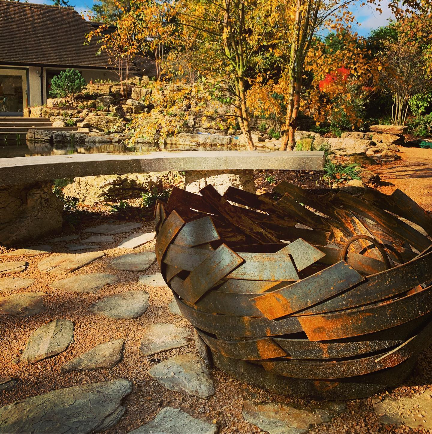 Beautiful handmade firepit by @magmafirepits in our client's garden reflecting its surroundings as it begins to take on its autumnal rusty tones... will post an update when it's fully rusted!
